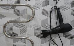 Stor tork för svart hår och handstång för handduk i hotellbadrum royaltyfri fotografi