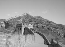 Stor vägg av Kina: Svartvitt skott av avsnittet med torn som spolar över en bergkant under en klar himmel Arkivfoton