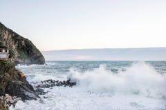 Stor våg som bryter över klippan på Riomaggiore, liguria under en stormig vinterdag royaltyfria foton