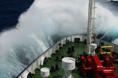 Stor våg som rullar över nosen av skeppet Arkivbild