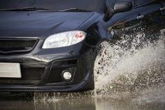 Stor vattenfärgstänk med bilen på den översvämmade vägen efter regn Arkivfoton
