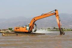Stor vattengrävskopa som muddrar bottensatsgyttja från floden Royaltyfri Foto