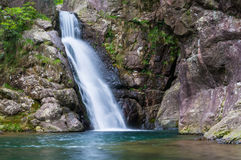 Stor vattennedgång i bergen med en sjö Arkivbilder