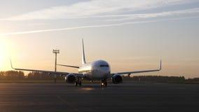 Stor vit nivå som förbereder sig att flyga att starta att flytta sig på landningsbana på solnedgången