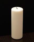 Stor vit stearinljus som isoleras på svart som står på trätabellen Arkivbild