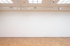 Stor vit vägg med trägolvtegelplattor Arkivbilder