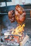 Stora stora bitar av läckra grisköttskinkor som lagas mat på en öppen brand Gatamaten Mat utomhus Campa och laga mat på a Royaltyfri Foto