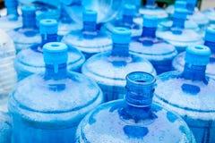 Stora blåa dricksvattentrummor, flaskor, gal., får våta i th Arkivfoton