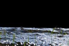 Stora blåsiga vågor som över plaskar, vaggar Vågfärgstänk i sjön som isoleras på svart bakgrund Vågor som bryter på en stenig str Arkivbilder