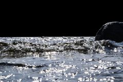 Stora blåsiga vågor som över plaskar, vaggar Vågfärgstänk i sjön som isoleras på svart bakgrund Vågor som bryter på en stenig str Royaltyfri Bild