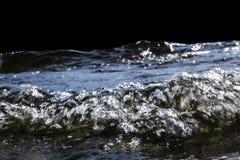 Stora blåsiga vågor som över plaskar, vaggar Vågfärgstänk i sjön som isoleras på svart bakgrund Vågor som bryter på en stenig str Royaltyfri Fotografi