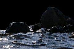 Stora blåsiga vågor som över plaskar, vaggar Vågfärgstänk i sjön som isoleras på svart bakgrund Vågor som bryter på en stenig str Arkivbild