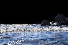 Stora blåsiga vågor som över plaskar, vaggar Vågfärgstänk i sjön som isoleras på svart bakgrund Vågor som bryter på en stenig str Arkivfoton