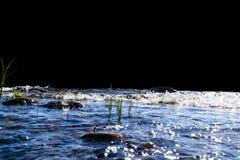 Stora blåsiga vågor som över plaskar, vaggar Vågfärgstänk i sjön som isoleras på svart bakgrund Vågor som bryter på en stenig str Royaltyfria Foton