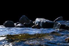 Stora blåsiga vågor som över plaskar, vaggar Vågfärgstänk i sjön som isoleras på svart bakgrund Vågor som bryter på en stenig str Arkivfoto