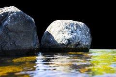 Stora blåsiga vågor som över plaskar, vaggar Vågfärgstänk i sjön som isoleras på svart bakgrund Vågor som bryter på en stenig str Royaltyfria Bilder
