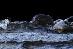 Stora blåsiga vågor som över plaskar, vaggar Vågfärgstänk i sjön som isoleras på svart bakgrund Vågor som bryter på en stenig str Royaltyfri Foto