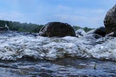 Stora blåsiga vågor som över plaskar, vaggar Vågfärgstänk i sjön mot stranden Vågor som bryter på en stenig strand som bildar en  Royaltyfri Fotografi