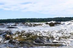 Stora blåsiga vågor som över plaskar, vaggar Vågfärgstänk i sjön mot stranden Vågor som bryter på en stenig strand som bildar en  Royaltyfri Foto