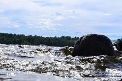 Stora blåsiga vågor som över plaskar, vaggar Vågfärgstänk i sjön mot stranden Vågor som bryter på en stenig strand som bildar en  Royaltyfria Bilder