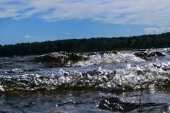 Stora blåsiga vågor som över plaskar, vaggar Vågfärgstänk i sjön mot stranden Vågor som bryter på en stenig strand som bildar en  Fotografering för Bildbyråer