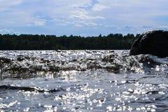 Stora blåsiga vågor som över plaskar, vaggar Vågfärgstänk i sjön mot stranden Vågor som bryter på en stenig strand som bildar en  Royaltyfria Foton