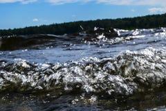 Stora blåsiga vågor som över plaskar, vaggar Vågfärgstänk i sjön mot stranden Vågor som bryter på en stenig strand som bildar en  Arkivbilder