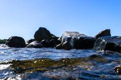 Stora blåsiga vågor som över plaskar, vaggar Vågfärgstänk i sjön mot stranden Vågor som bryter på en stenig strand som bildar en  Royaltyfri Bild