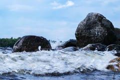 Stora blåsiga vågor som över plaskar, vaggar Vågfärgstänk i sjön mot stranden Vågor som bryter på en stenig strand som bildar en  Arkivfoton