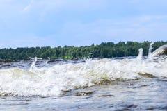 Stora blåsiga vågor som över plaskar, vaggar Vågfärgstänk i sjön mot stranden Vågor som bryter på en stenig strand som bildar en  Arkivbild