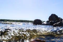 Stora blåsiga vågor som över plaskar, vaggar Vågfärgstänk i sjön mot stranden Vågor som bryter på en stenig strand som bildar en  Arkivfoto