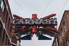 Stora Carnaby och Union Jack 3D skimrar undertecknar över föreningspunkten mellan den Carnaby gatan och den Ganton gatan, London, Royaltyfri Fotografi