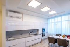 Stora fönster för vitt köksbord royaltyfria foton