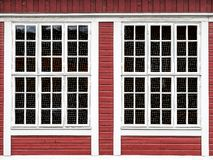 Stora fönster på en röd trävägg arkivbilder