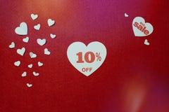 Stora försäljningar, tio procent i en vit hjärta på röd bakgrund för reklambladet, affisch royaltyfria bilder