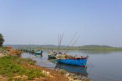 Stora gamla fiskebåtar med motorer och metspön som ankras av kusten mot bakgrunden av en flod och en grön skog royaltyfri fotografi