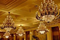 Stora guld- tappningkristallkronor på taket i den rika korridoren royaltyfri bild
