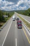 Stora halva lastbilar reser ner huvudvägen Royaltyfri Bild