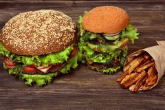 Stora hamburgare med pommes frites för ett snabbt mellanmål Fotografering för Bildbyråer