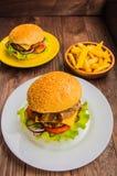 Stora hamburgare- och fransmansmåfiskar på en trätabell i lantlig stil Närbild Royaltyfria Bilder