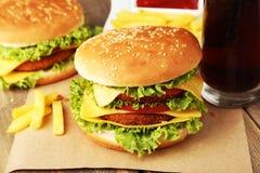 Stora hamburgare på brun träbakgrund Fotografering för Bildbyråer