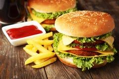 Stora hamburgare på brun träbakgrund Arkivfoton