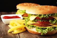 Stora hamburgare på brun träbakgrund Royaltyfria Bilder