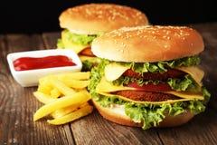 Stora hamburgare på brun träbakgrund Royaltyfri Foto