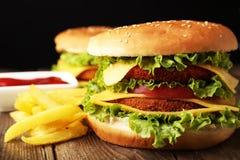 Stora hamburgare på brun träbakgrund Royaltyfri Fotografi