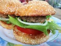 Stora hamburgare på plattan Royaltyfria Bilder