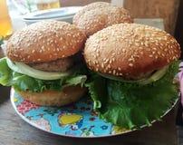 Stora hamburgare på plattan Arkivbild