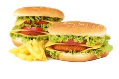 Stora hamburgare som isoleras på vit Royaltyfria Foton