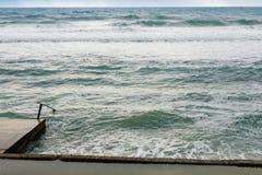 Stora havsvågor som bryter på den konkreta pir i blåsväder royaltyfri fotografi