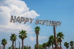 Stora heliumballongbokstäver i luften som firar lycklig födelsedag med, gömma i handflatan utomhus och blå himmel royaltyfri foto